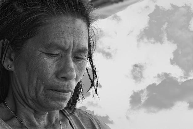 Grijswaardenfoto van oudere vrouw die voedsel bereidt onder een buitenluifel in de filippijnen