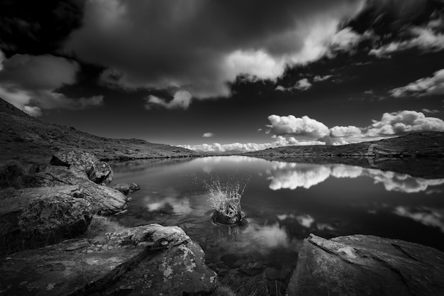 Grijswaardenopname van een meer omringd door bergen onder de hemel vol wolken