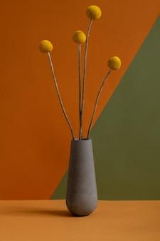 Grijze aarden kruik of vaas met verschillende gele gedroogde wilde bloemen met lange stelen die op bruine tafel op een dubbele kleur muur staan