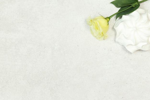 Grijze achtergrond met roos en marshmallow