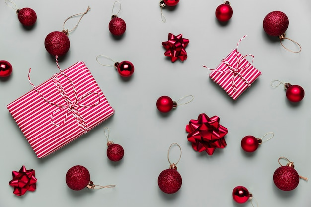 Grijze achtergrond met twee roze kerstcadeautjes, kleine rode kerstballen of bolspeelgoed, lintbogen voor dennenboom. concept voor feestelijke verkoop, promoties, wenskaarten of uitnodigingsfoto's
