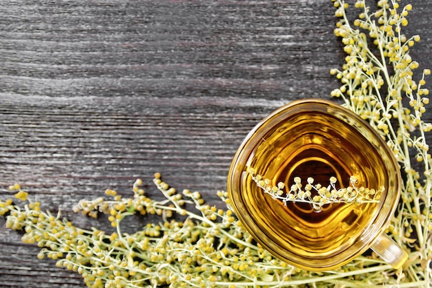 Grijze alsem kruidenthee in een glazen beker, verse alsem bloemen op een houten bord van bovenaf