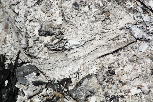 Grijze astextuur, sintel, grijze as van het hout van de open haard.