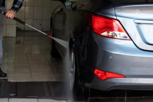 Grijze autowasserette met water. contactloze gootsteen. autowasserette zelfbediening