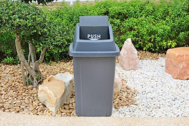 Grijze bak voor algemeen afval in openbare tuin