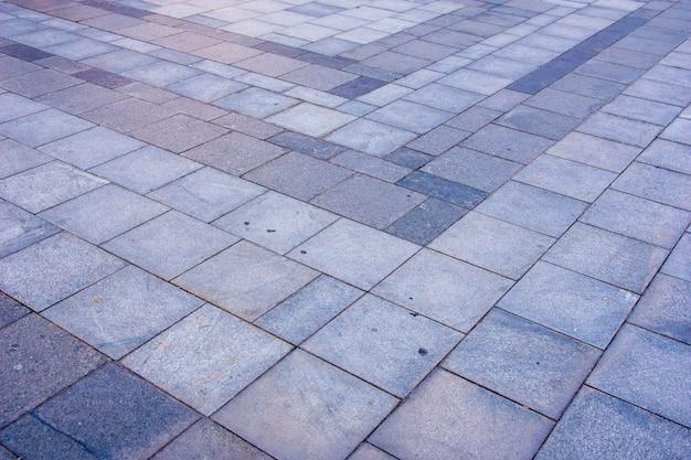 Grijze bakstenen bestrating in de stad in diagonaal