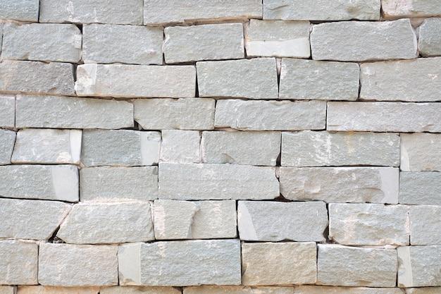 Grijze bakstenen muur en ruwe de muurachtergrond van de zandsteen