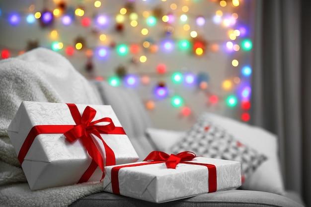Grijze bank met geschenken op de achtergrond van kerstverlichting