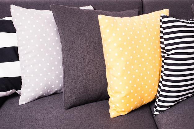 Grijze bank met veel kleurrijke kussens erop