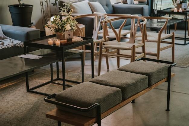 Grijze bank met zeer moderne houten stoelen en tafels, versierd met kaarsen, planten en bloemen.