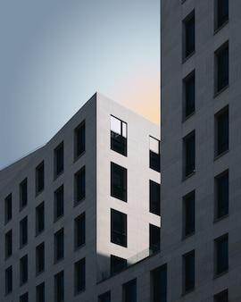 Grijze betonnen gebouw onder de blauwe hemel