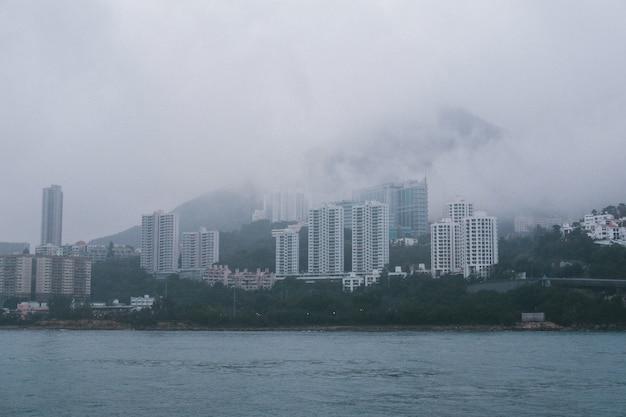 Grijze betonnen hoge wolkenkrabbers aan de kust bij mistig weer