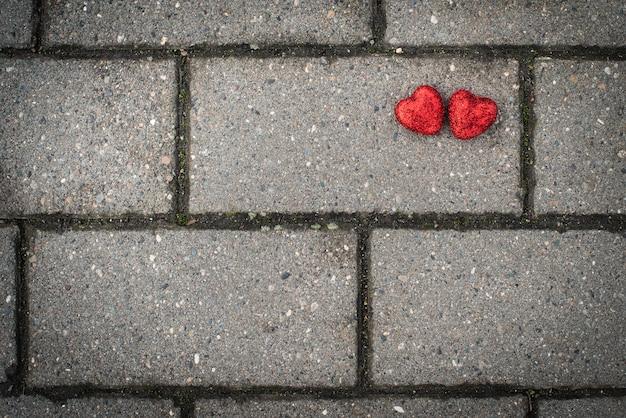 Grijze betonnen tegels op de vloer en twee rode harten. ruimte voor tekst, ruimte voor kopiëren, plat geblaf.