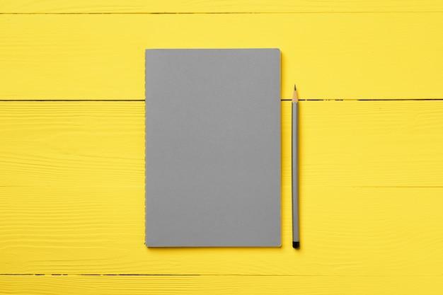 Grijze blocnote met potlood op gele houten hoogste mening als achtergrond