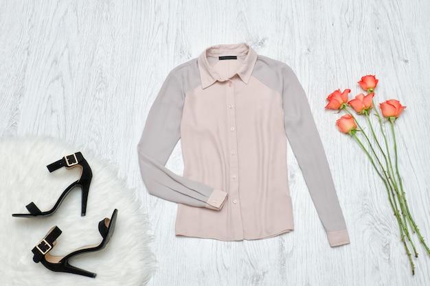 Grijze blouse, zwarte schoenen en oranje rozen