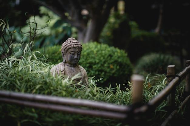 Grijze boeddha in de buurt van standbeeld in de buurt van groene planten