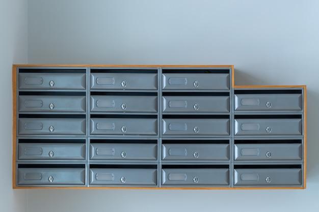 Grijze brievenbussen op de blauwe muur van ingang van flatgebouw