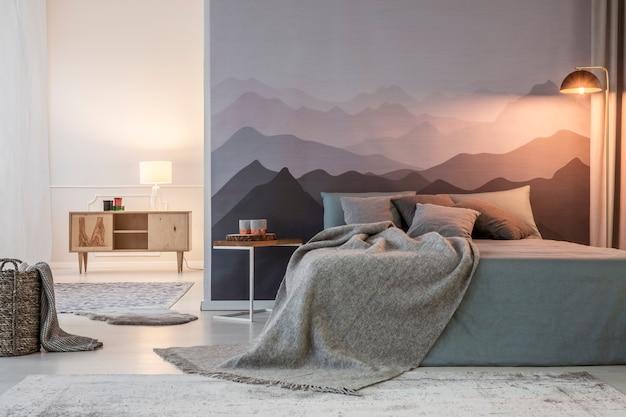 Grijze deken op bed tegen bergbehang naast een kruk met licht in slaapkamerinterieur