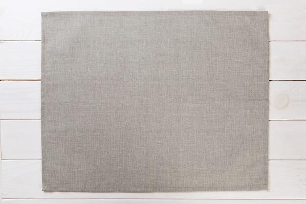 Grijze doek servet op witte rustieke houten achtergrond bovenaanzicht met kopie ruimte.