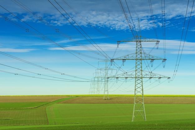 Grijze elektrische post onder witte en blauwe bewolkte hemel