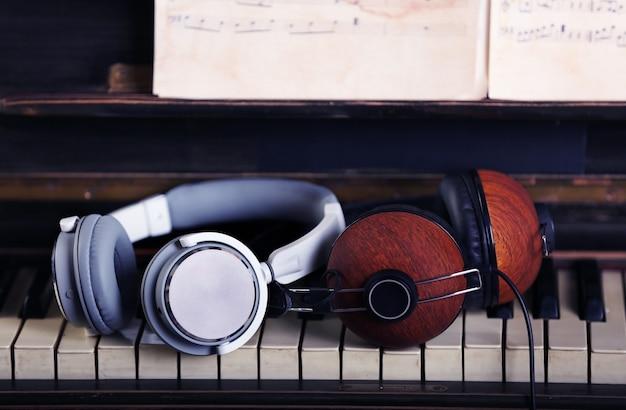 Grijze en bruine hoofdtelefoons op pianotoetsenbord