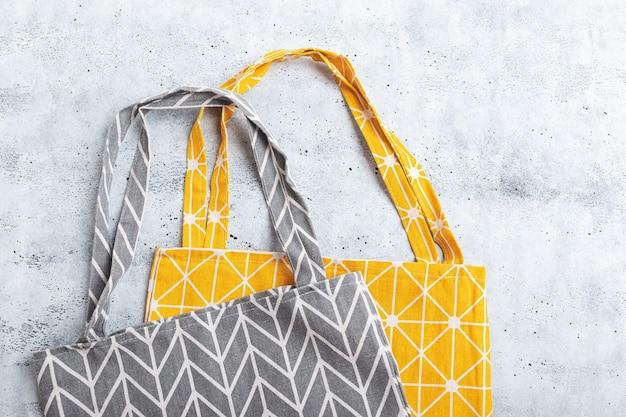 Grijze en gele shopper tassen op betonnen ondergrond. kunststofvrij. milieuvriendelijk