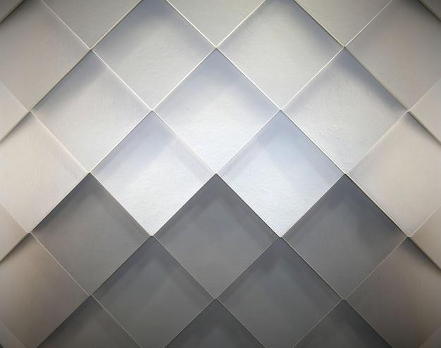 Grijze en witte tegels gerangschikt op de muur in diagonaal rechthoekig patroon.