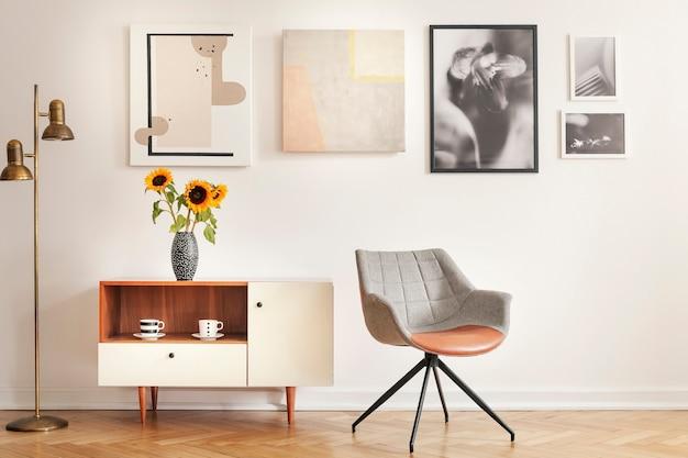 Grijze fauteuil naast kast met zonnebloemen in wit kamerinterieur met galerij. echte foto