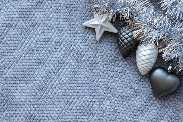 Grijze gebreide textuur met zilveren klatergoudslinger en kerstboomspeelgoed
