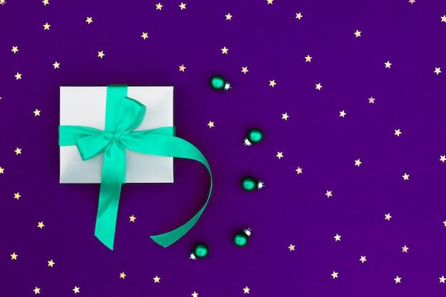 Grijze geschenkdoos met een groene satijnen strik en kleine balletjes op violet met veel kleine sterren.