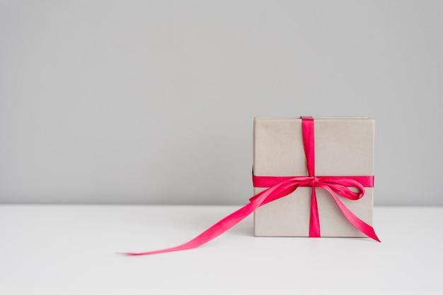 Grijze geschenkdoos met roze strik en lint op grijze achtergrond