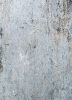 Grijze geschilderde muurtextuur met barsten