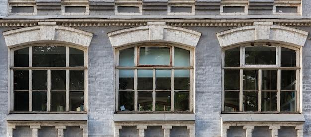Grijze gevel van een historisch gebouw met drie boogramen