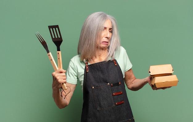 Grijze haar mooie barbecue chef-kok vrouw