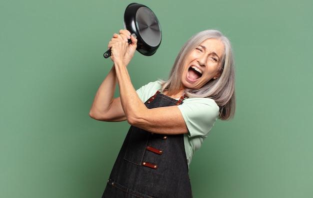 Grijze haar mooie chef-kokvrouw van middelbare leeftijd met een pan