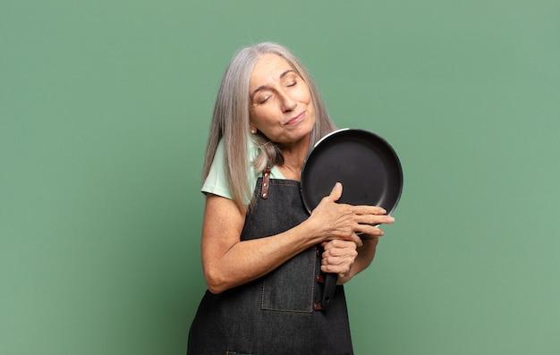 Grijze haar mooie middelbare leeftijd chef-kok vrouw met een pan