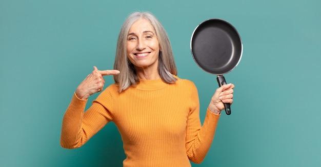 Grijze haar mooie middelbare leeftijd vrouw leren koken met een pan