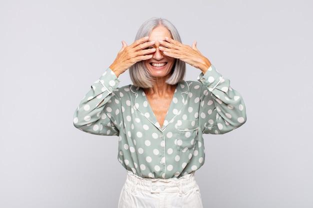 Grijze haired vrouw die en gelukkig glimlacht voelt, ogen bedekt met beide geïsoleerde handen