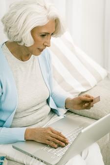 Grijze haired vrouw die laptop voor online het winkelen met behulp van