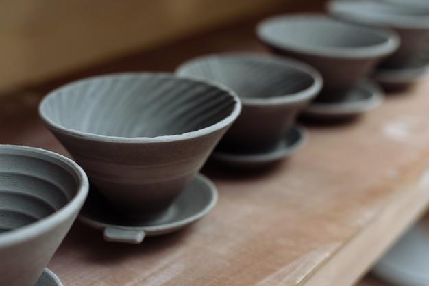 Grijze handgemaakte keramische platen. geglazuurde kleiplaten in een pottenbakkerij.