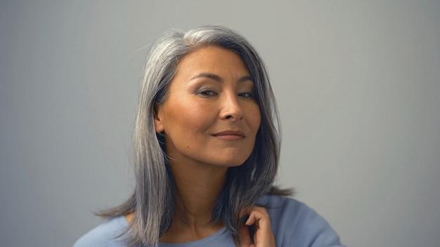 Grijze haren aziatische vrouw met een mysterieuze uitdrukking op haar gezicht