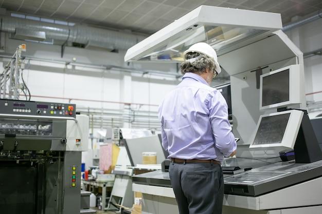 Grijze haren mannelijke plant ingenieur in veiligheidshelm en glazen staan op industriële machine, met behulp van digitaal apparaat