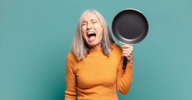 Grijze haren mooie middelbare leeftijd vrouw leren koken met een pan