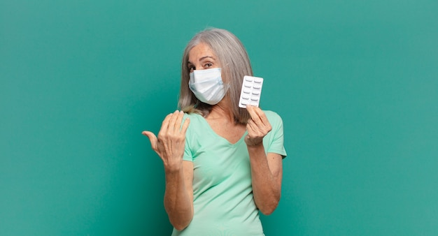 Grijze haren mooie vrouw met een beschermend masker en pillen