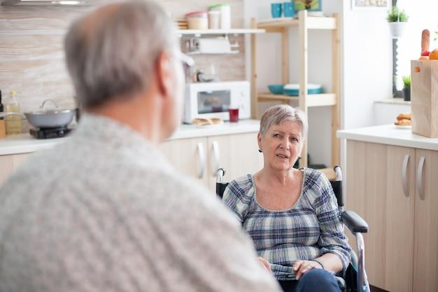 Grijze harige man chatten met verlamde vrouw. gepensioneerde ongeldige vrouw in rolstoel die een gesprek heeft met oude bejaarde echtgenoot in keuken. oude man praten met vrouw. leven met gehandicapte met