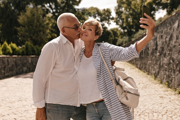 Grijze harige man in wit overhemd en spijkerbroek is gefotografeerd en kuste haar vrouw met kort haar in gestreepte blouse met rugzak in park.
