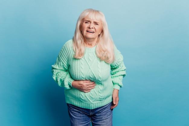 Grijze harige oude vrouw lijdt aan buikpijn over blauwe achtergrond