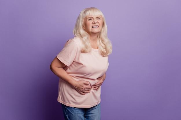Grijze harige oude vrouw lijdt aan buikpijn over violette achtergrond