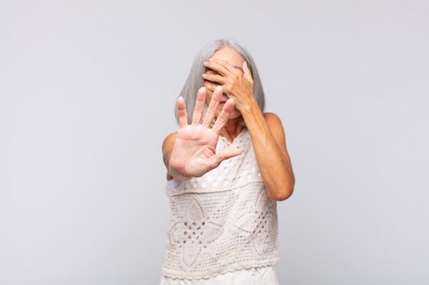 Grijze harige vrouw die gezicht bedekt met hand en andere hand vooraan zet