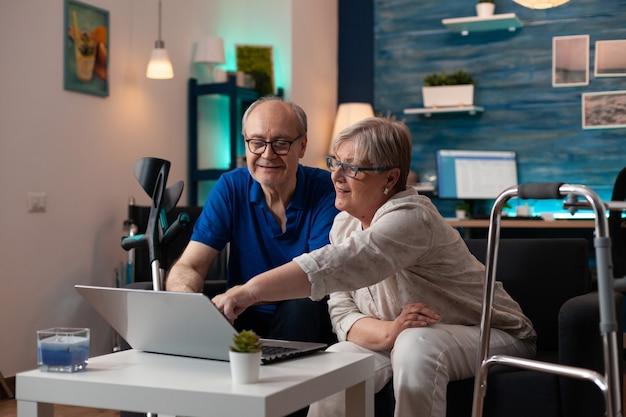 Grijze harige vrouw oude man die laptop scherm analyseert